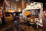 Boston, MA 12/08/2011.Occupy Boston members fill a waiting garbage truck as the city of Boston's deadline to vacate Dewey Square draws near on Thursday evening..Alex Jones / www.alexjonesphoto.com