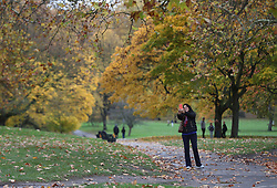 A woman takes a selfie with the autumn trees in Green Park, London.