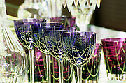 In the shop show room. Crystal glasses blue and purple with reflections from the table. At The Baccarat museum, shop, restaurant at the Hotel de Noailles in Paris. Designed by Philippe Starck. The Baccarat shop: glasses on display. The glasses are actually plain blue. The pattern is a reflection of the crystal table