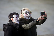 A couple wearing Anonymous masks pose for their own selfie photo. Holding up a smartphone to take the picture, the person on the right touches the keypad to trigger the device. They both look young, possibly tourists but we don't see their faces or expressions as they stand on the south bank of the river Thames in central LOndon.