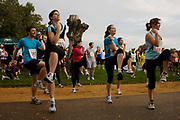 Amateur running club athletes warm-up with group aerobics before a 10k race in Dulwich Park, South London. Encouraged by a keep-fit instructor who is urging them on to perform these beneficial exercised before their race, the women and some men touch elbows on knees to this choreographed dance helping them to loosen up and relax tense muscles, helping to ease sore joints later. Wearing numbers and most in running shirts, leggings and runners' trainer shoes, they jump and stretch with a sense of health and fun.