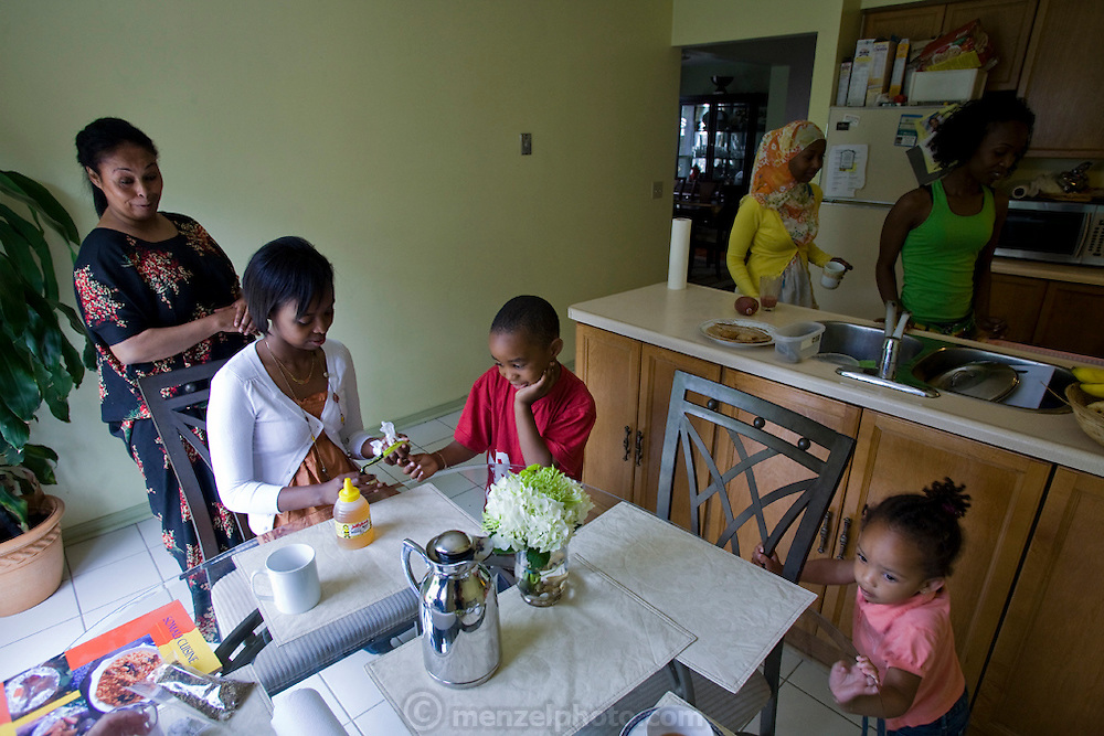 Muna Ali  (in white sweater) plays with her siblings in the kitchen of her parents' house in Scarboro, Ontario, Canada. She and her family immigrated from Somalia .