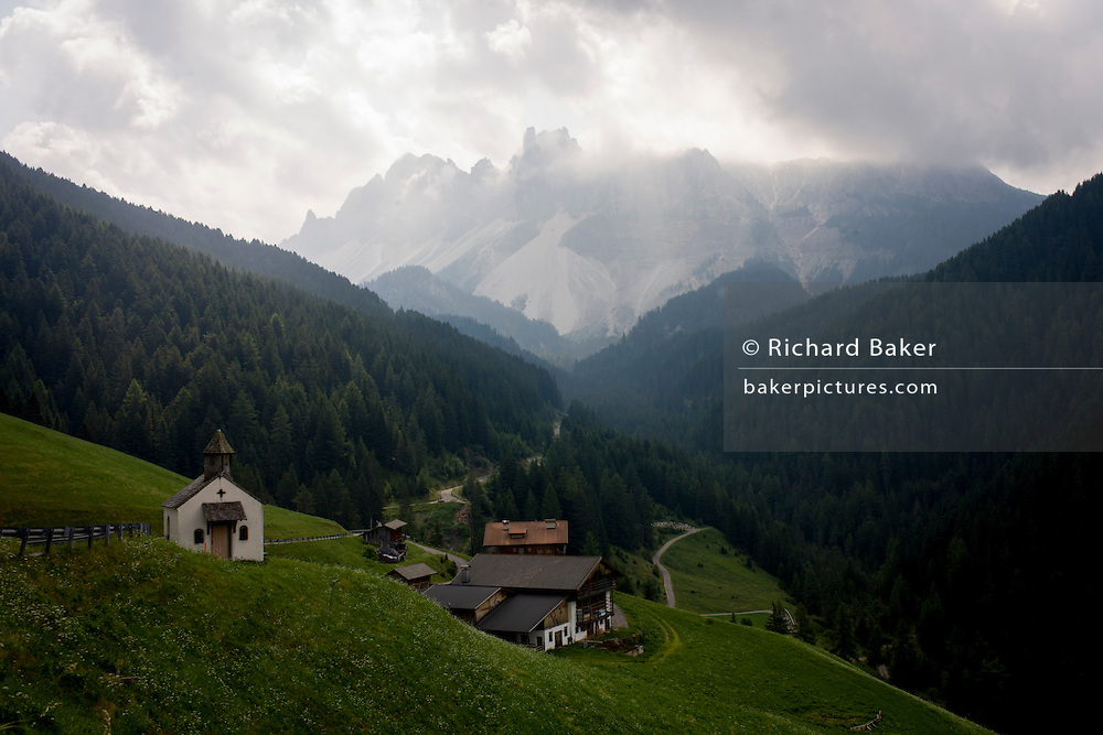 Hamlet's chapel with presence of huge Dolomites mountains of the Puez Geisler range in the south Tyrol, Italy.