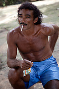 Indigenous Brazilian man sitting on a rack with a cigarette in his mouth. A third of Altamira in the state of Para, Brazil will be flooded to make way for the Belo Monte dam, nearly all the people affected are the poorest in society or indigenous communities that will have nowhere to go if they were made homeless, and the Government payoff for their properties is low therefore making it difficult to find new accomodation.