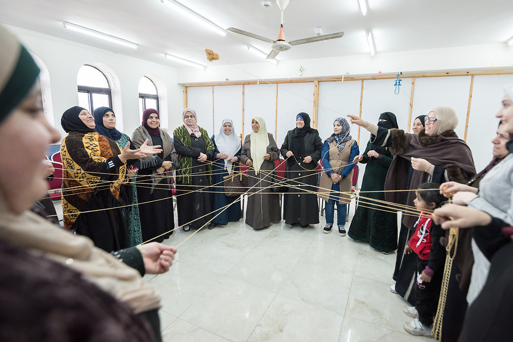 16 February 2020, Irbid, Jordan: Women play a game to learn each others names at the beginning of a caregiver support session led by the Lutheran World Federation at the Islamic Centre in Al-Mazar, offering psychosocial support to Syrian refugee mothers and Jordanian host communities.
