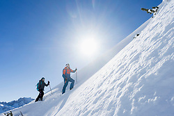 Couple climbing up the ski slope in Upper Bavaria, Germany, Europe