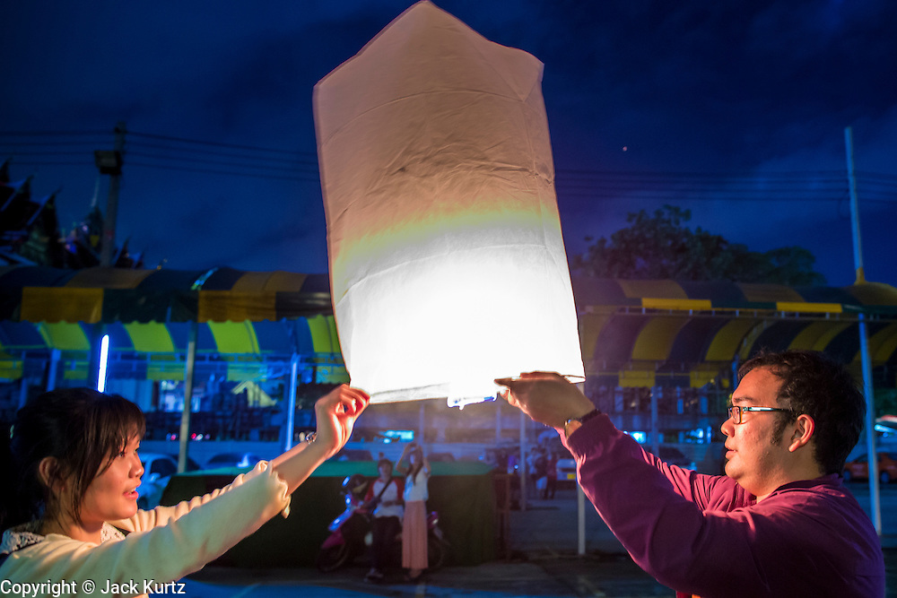 28 NOVEMBER 2012 - BANGKOK, THAILAND: People try to light a Khom Loi lantern  during Loy Krathong at Wat Yannawa in Bangkok. The lanterns are a part of the Loy Krathong tradition in northern Thailand, and are becoming popular in Bangkok. But authorities don't allow their use in Bangkok because of the fire danger. They try to stop people from launching the lanterns in Bangkok. Loy Krathong takes place on the evening of the full moon of the 12th month in the traditional Thai lunar calendar. In the western calendar this usually falls in November. Loy means 'to float', while krathong refers to the usually lotus-shaped container which floats on the water. Traditional krathongs are made of the layers of the trunk of a banana tree or a spider lily plant. Now, many people use krathongs of baked bread which disintegrate in the water and feed the fish. A krathong is decorated with elaborately folded banana leaves, incense sticks, and a candle. A small coin is sometimes included as an offering to the river spirits. On the night of the full moon, Thais launch their krathong on a river, canal or a pond, making a wish as they do so.    PHOTO BY JACK KURTZ