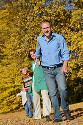 Family walking in autumn leaves, smiling