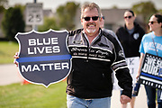 """19 SEPTEMBER 2020 - ALTOONA, IOWA: BRIAN MILLARD, left, and JANA MILLARD march with other pro-police ralliers near the police station in Altoona, a suburb of Des Moines. About 30 people attended an """"Uplifting Our Police"""" rally to show support for not just Altoona police, but law enforcement across the country.      PHOTO BY JACK KURTZ"""