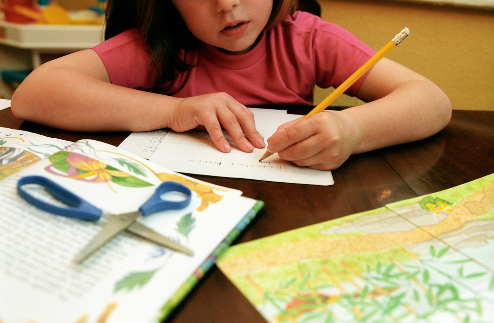 Young girl writing with her left hand,