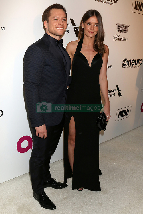 February 24, 2019 - West Hollywood, CA, USA - LOS ANGELES - FEB 24:  Taron Egerton, Emily Thomas at the Elton John Oscar Viewing Party on the West Hollywood Park on February 24, 2019 in West Hollywood, CA (Credit Image: © Kay Blake/ZUMA Wire)