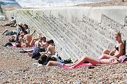 © Licensed to London News Pictures. 06/06/2015. Brighton, UK. People are sunbathing on Brighton Beach. Thousands of people are expected to visit Brighton and the South Coast with temperatures expected to be the hottest of the year so far. today June 6th 2015. Photo credit : Hugo Michiels/LNP