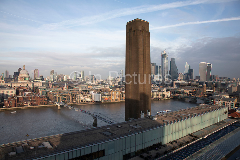 View over the River Thames towards St Pauls Cathedral and the City of London from the Blavatnik Building Viewing Level at Tate Modern art gallery in London, England, United Kingdom. The building, originally Bankside Power Station, was designed by the architect Sir Giles Gilbert Scott. Constructed from a brick shell supported by an interior steel structure, its striking monumental design with its single central chimney, had often led it to be referred to as an industrial cathedral. The 360-degree rooftop viewing deck is one of the headline features of the Switch House – the 64.5-metre-high Tate Modern gallery extension by Herzog & de Meuron, opened to the public in June 2016.