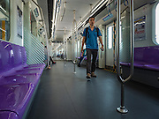 "23 AUGUST 2016 - NONTHABURI, NONTHABURI, THAILAND: A passenger walks through a nearly empty train car on the ""Purple Line,"" the new Bangkok commuter rail line that runs from Bang Sue, in Bangkok, to Nonthaburi, a large Bangkok suburb. The Purple Line is run by the  Metropolitan Rapid Transit (MRT) which operates Bangkok's subway system. The Purple Line is the fifth light rail mass transit line in Bangkok and is 23 kilometers long. The Purple Line opened on August 6 and so far ridership is below expectations. Only about 20,000 people a day are using the line; officials had estimated as many 70,000 people per day would use the line. The Purple Line was supposed to connect to the MRT's Blue Line, which goes into central Bangkok, but the line was opened before the connection was completed so commuters have to take a shuttle bus or taxi to the Blue Line station. The Thai government has ordered transit officials to come up with plans to increase ridership. Officials are looking at lowering fares and / or improving the connections between the two light rail lines.     PHOTO BY JACK KURTZ"