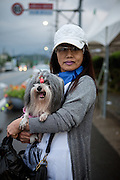 A woman is holding her dog close to the city of Yeosu located at the Korean South Coast.