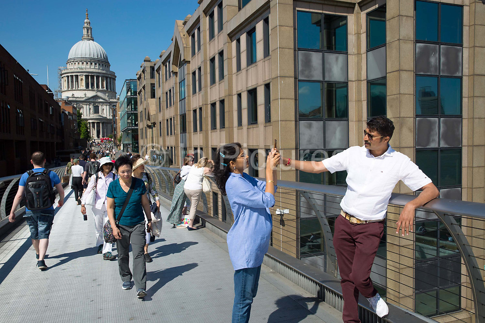 A man helps his partner take a selfie on a mobile phone 25th May 2017 in London, United Kingdom. Captured on Millennium Bridge with St Pauls Cathedral on the horizon. From the series Our Small World, an observation of our mobile phone obsessions