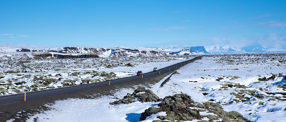 Cars motoring by volcanic lava mounds field like lunar landscape between Vik and Kirkjubaejarklaustur by Katla volcano in South Iceland