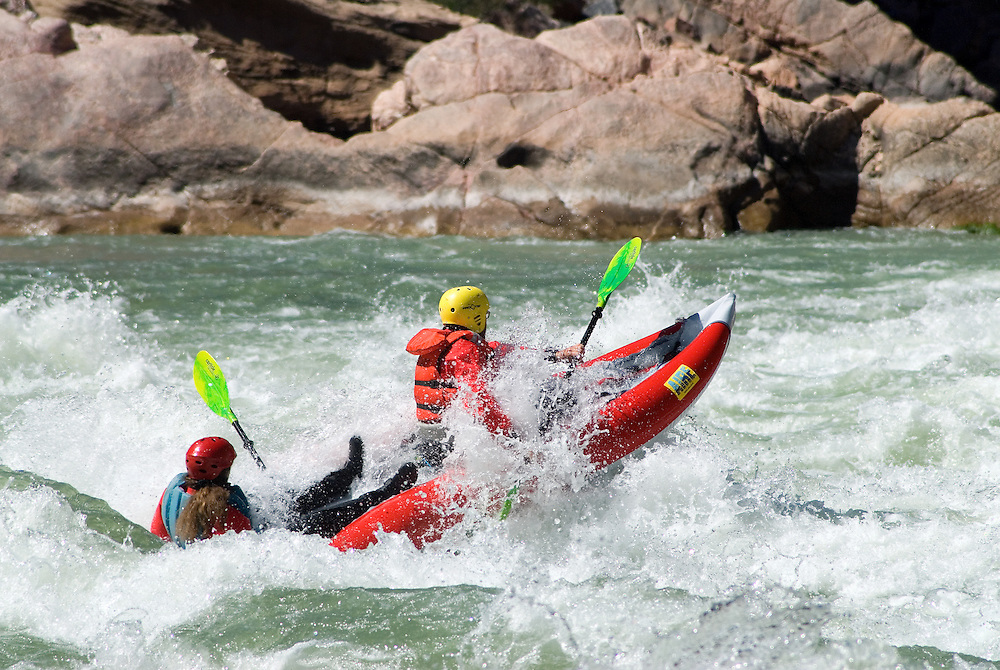 Paddling an inflatable kayak through a rapid on the Colorado River in the Grand Canyon, Arizona.