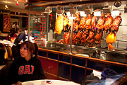 Girl waiting for her partner at a Chinese restaurant during Chinese New Year on Gerrard Street, Soho, London. Also known as Chinatown. Local Chinese community gather in this famous area of central London which is the focus of celebrations for this, the Chinese Year of the Dragon, so a most auspicious year ahead.