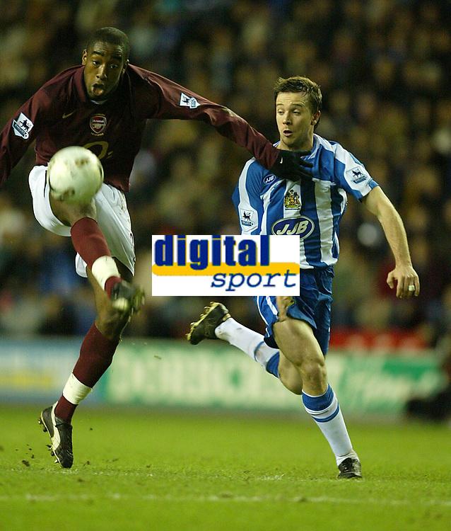 Photo: Aidan Ellis.<br /> Wigan Athletic v Arsenal. Carling Cup. Semi Final, 1st Leg.<br /> 10/01/2006.<br /> Arsenal's Johan Djourou beats Wigan's David Connolly to the ball