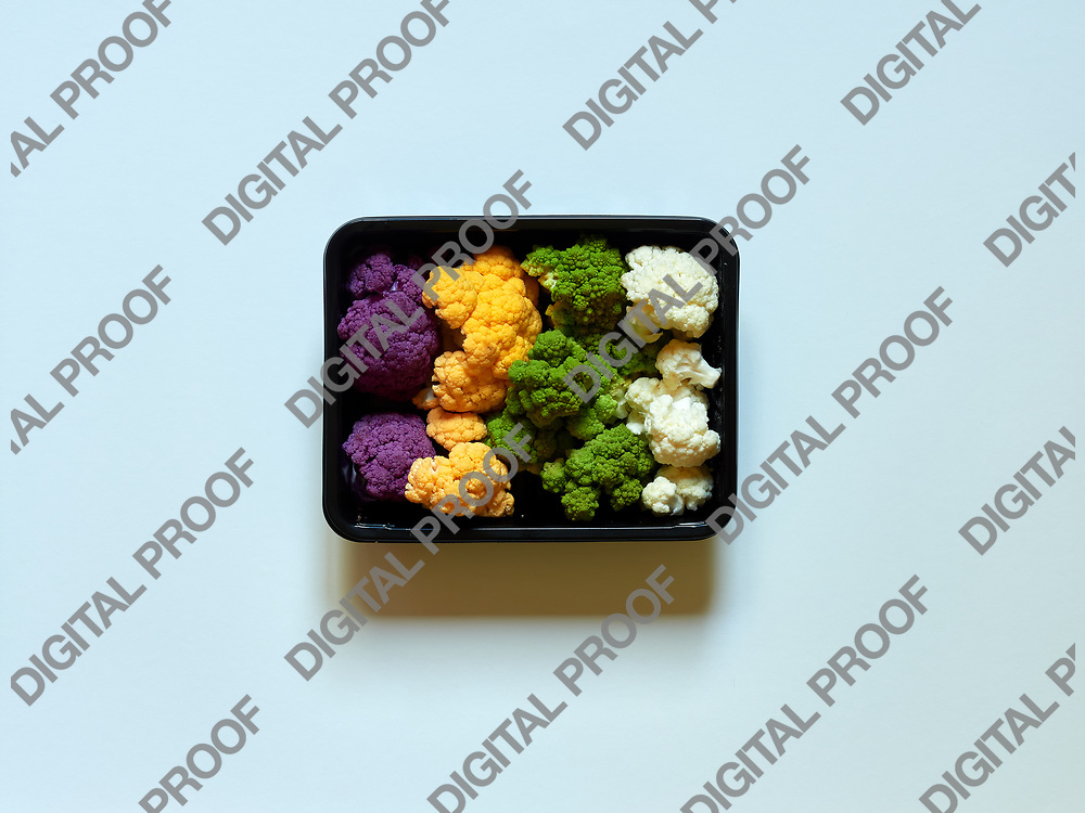 Set of seasonal and colorful cauliflower violet, yellow, green and white boxed in a plastic recipient over a white background