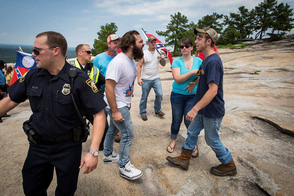 An anti-Confederate flag protester, Tommy, (only gave his first name) is confronted by a man attending a Confederate flag rally at Stone Mountain Park in Stone Mountain, Georgia on Saturday, Aug. 1, 2015. Photo by Kevin Liles/kevindliles.com