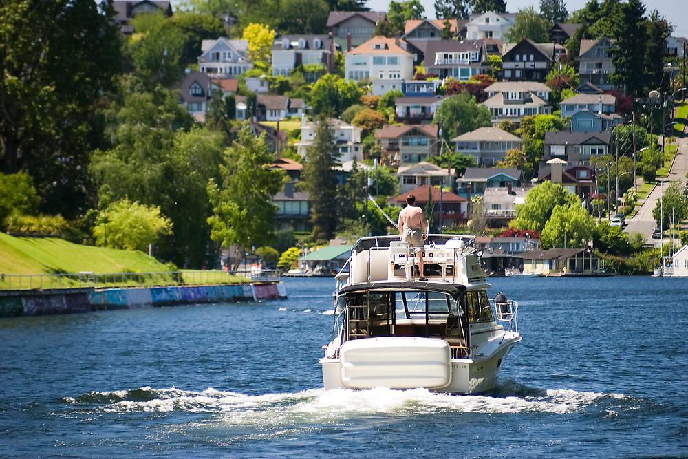 A man drives his boat through the Montlake Cut in Seattle, Washington.
