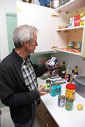 White older man putting away shopping