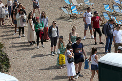 © Licensed to London News Pictures. 30/05/2021. Brighton, UK. A long queue for toilet on the Brighton seafront on the hottest day of the year so far. According to the Met Office, a high of 24 degrees celsius is forecast for the bank holiday weekend, after weeks of rain in the South East of England.  Photo credit: Dinendra Haria/LNP