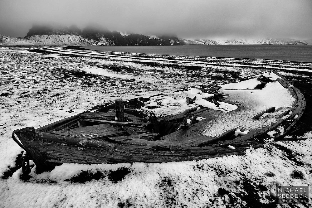 An old derelict wooden whaling boat lies just behind the beach at the old  whaling station of Deception Island.<br /> <br /> Limited Edition Print