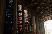 Interior looking towards the entrance Great West Window of Coventry Cathedral also known as St Michaels, a modern cathedral founded in 1956 and well known for having stunning modernist stained glass, minimalist structure and large scale tapestry on 23rd June 2021 in Coventry, United Kingdom. The Cathedral Church of Saint Michael, commonly known as Coventry Cathedral, is the seat of the Bishop of Coventry and the Diocese of Coventry within the Church of England. The current St Michaels Cathedral, built next to the remains of the old, was designed by Basil Spence and Arup, built by John Laing and is a Grade I listed building.
