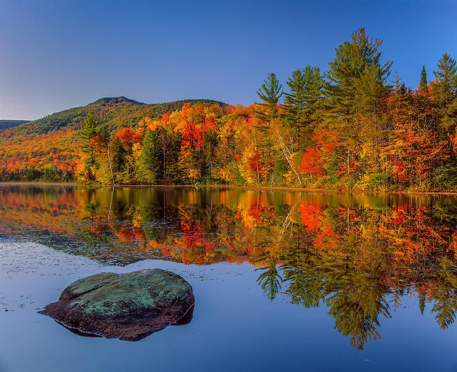 Large boulder in pond and strong light on fall foliage shoreline, Chittenden, VT