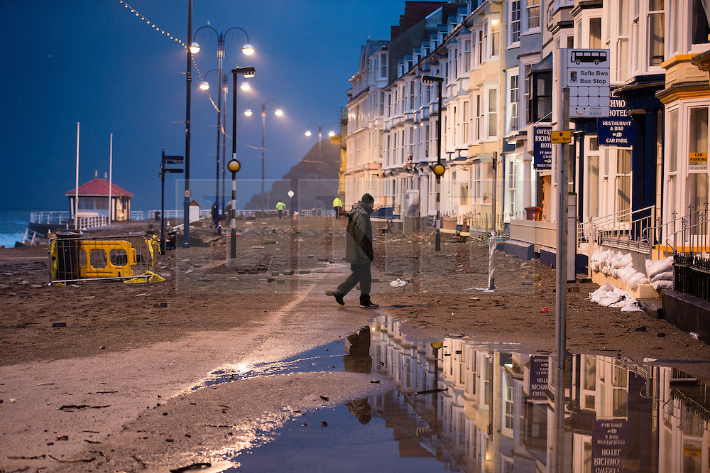 © Licensed to London News Pictures. 04/01/2014. Aberystwyth, UK At first light on saturday 4 Jan 2014 the damage done to the promenade at Aberystwyth is clear to see. Hundreds off tons of sand and gravel has been dumped on the roadway, along with  huge chunks of the promenade pavement and railings.. Photo credit : Keith Morris/LNP