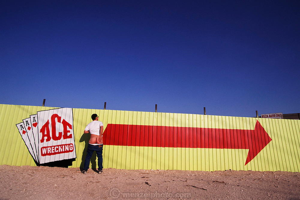 A photo assistant exposes his butt by a sign for the Ace Wrecking Company. Ace Auto salvage yard outside El Paso, Texas, USA. MODEL RELEASED.