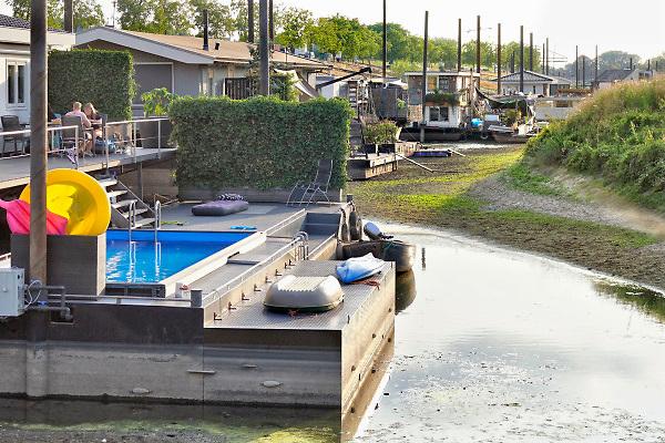Nederland, Beneden Leeuwen, 4-8-2018In een leeggelopen strang van de Waal liggen woonschepen op het droge, op de bodem .Door de droogte in heel europa is het peil van de rivier zo laag dat de inham droog staat .Foto: Flip Franssen