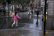 During an early evening downpour, a woman wearing a pink jumper runs across a pedestrian crossing in SLoane Square, on 24th August 2020, in London, England.