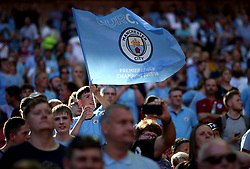 Manchester City's fans at full time wave a flag