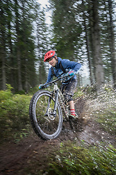 Mountain biker rides through a puddle in forest on rainy day, Saalfelden, Tyrol, Austria