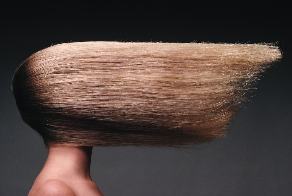 Woman with long, straight blond hair that is defying gravity because it is going out horizontally from, and covering her face