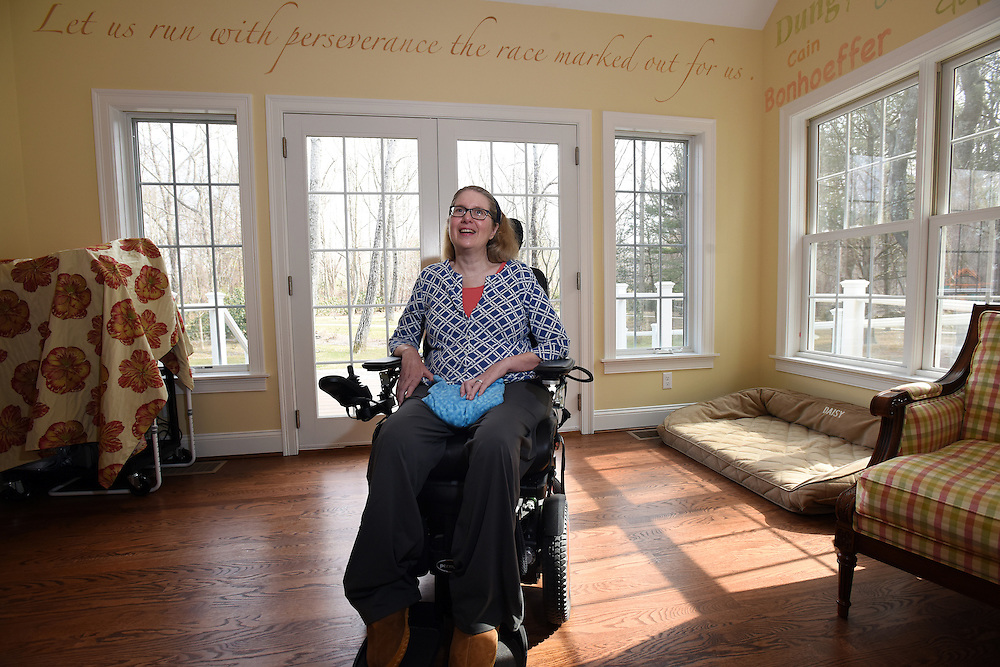 """Mara Lavitt -- Special to the Hartford Courant<br /> March 7, 2016, Marlborough<br /> Pastor Nancy Butler at home in her Marlborough bedroom March 7. Above her is a passage from the bible. """"It's from the book of Hebrews,"""" she said. """"And the early Christians were being persecuted, and they were quitting the church because it was so difficult."""" The whole book of Hebrews was written to bolster suffering people, she explained. """"That verse from Hebrews, that kind of gives me a kick in the pants when I need it."""" On the wall, right, are the names of those who inspire her."""