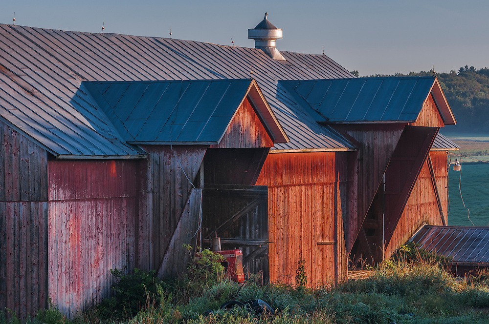 Details of red weathered wood sided barn in strong first light, Franklin, VT