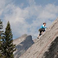 A rock climber ascends Rundle rock near Banff in Banff National Park, Alberta, Canada. Cascade Mountain is behind.