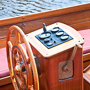 wooden steering wheel and dashboard of a boat on a river
