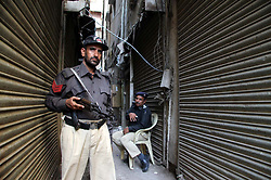 April 25, 2017 - Karachi, Pakistan - Law and enforcement officials cordon off the site after an hours long fire exchange between militants and the paramilitary forces in raid a residential building near Urdu Bazar area. Four terrorists, including a woman, were killed and four paramilitary personnel injured in a gunfight between Rangers and militants holed up inside a residential building. (Credit Image: © PPI via ZUMA Wire)