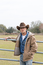 good looking cowboy standing by a fence on a ranch