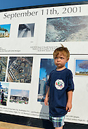 """East Meadow, New York, U.S. 11th September 2013. TIMOTHY HUNTER, 3, of Wantagh, visits the Global War on Terror """"Wall of Remembrance"""" a traveling memorial on display in New York for the first time, at Eisenhower Park on the 12th Anniversary of the terrorist attacks of 9/11. Timothy's uncle Joseph G. Hunter, a firefighter in Squad 288 in Maspeth Queens, died during September 11th 2001 terrorist attack, and the nephew is wearing a T-shirt from the 9th Annual Memorial Drill for his Uncle Joseph. The unique 94 feet long by 6 feet high wall has, on one side, almost 11,000 names of those lost on September 11th 2001, along with heroes and veterans who lost their lives defending freedom of Americans over past 30 years. On the wall's other side is a timeline, with photos, covering 1983 to present day."""