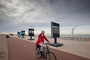 Nederland, Scheveningen, 01-11-2018<br /> Op de boulevard bij het strand van Scheveningen rijden fietsers langs de tentoonstelling Where Will We Go van Kadir van Lohuizen over de effecten van de stijgende zeespiegel.<br /> <br /> At the boulevard at the beach of Scheveningen cyclists pass the photo exhibition Where Will We Go on the effects of the rising sea level by Kadir van Lohuizen.<br /> Foto: Bas de Meijer / De Beeldunie