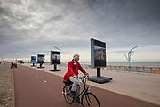 Nederland, Scheveningen, 01-11-2018<br /> Op de boulevard bij het strand van Scheveningen rijden fietsers langs de tentoonstelling Where Will We Go van Kadir van Lohuizen over de effecten van de stijgende zeespiegel.<br /> <br /> At the boulevard at the beach of Scheveningen cyclists pass the photo exhibition Where Will We Go on the effects of the rising sea level by Kadir van Lohuizen.<br /> Foto: Bas de Meijer / De Beeldunie