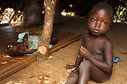 A boy sits on the ground while his younger sibling lies on a mat inside the basic shelter made of palm leaves where they live after their home was destroyed by floods in the village of Kpoto, Benin on Wednesday October 27, 2010.