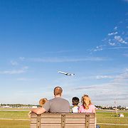 A family watches planes take off and land at the Charlotte-Douglas International airport overlook.